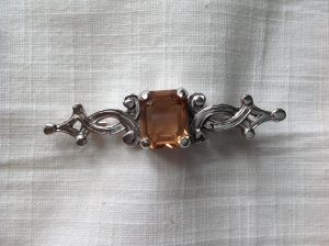 Silver tone Celtic style stock pin with citrine coloured glass